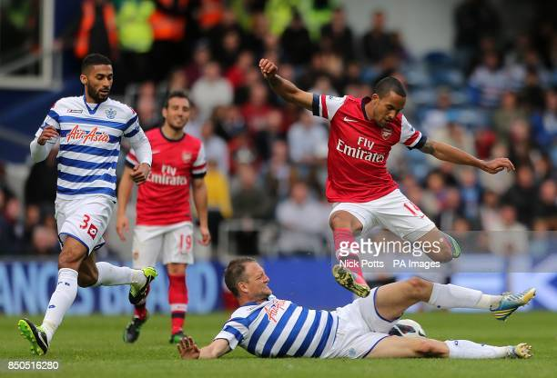 Queens Park Rangers' Clint Hill slides in on Arsenal's Theo Walcott