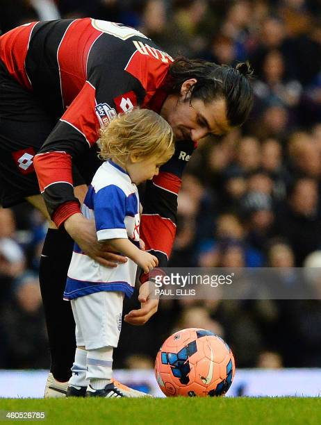 Queens Park Rangers' English midfielder Joey Barton and his son who was team mascot look on before the English FA cup third round football match...
