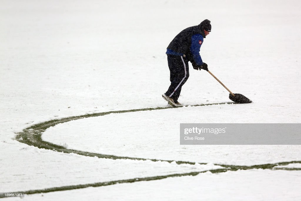 Queens Park Rangers ground staff clear the snow off pitch lines prior to a training tession and press conference on January 18, 2013 in Harlington, England.