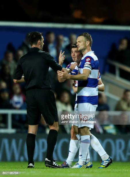 Queens Park Rangers' Joey Barton and captain Clint Hill argue a point with referee Mr Andrew Madley during the Sky Bet Championship match at Loftus...