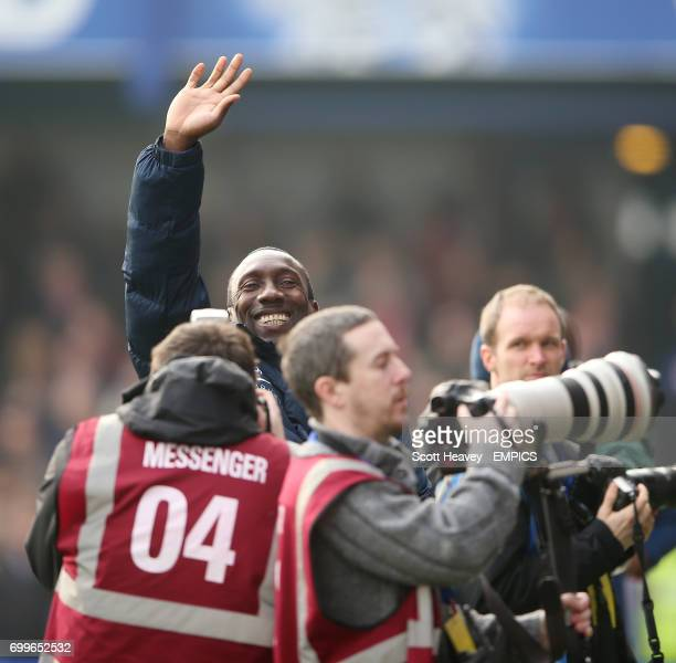 Queens Park Rangers manager Jimmy Floyd Hasslebaink waves beyond photographers before the game