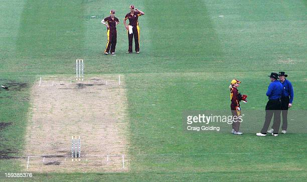 Queensland Fire captain Jodie Fields talks with umpires after they called a halt to play due to the weather during the WNCL Final match between the...