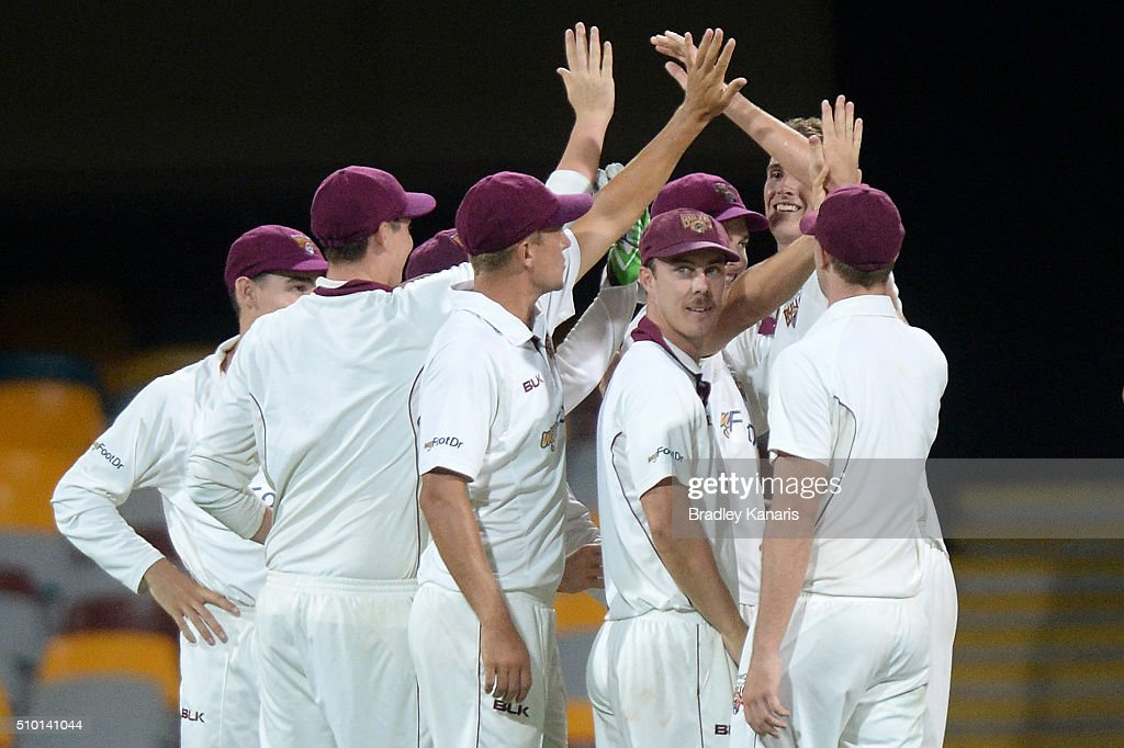 Queensland players celebrate after Ben McDermott of Tasmania is caught by Jack Wildermuth off the bowling of Peter George of Queensland during day one of the Sheffield Shield match between Queensland and Tasmania at The Gabba on February 14, 2016 in Brisbane, Australia.