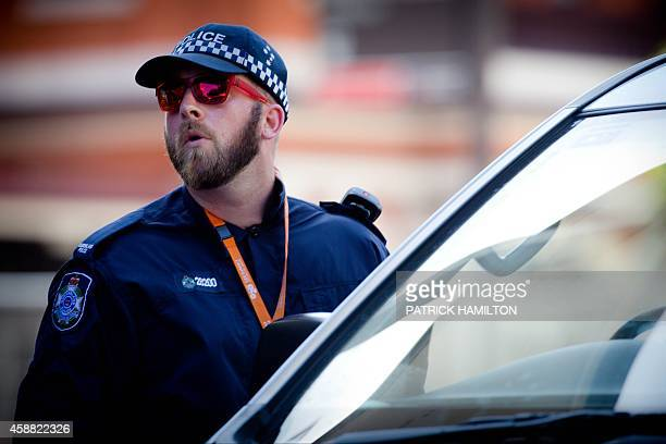 A Queensland police officer check vehicles at an entrance to the G20 Precinct near the Brisbane Exhibition and Convention Centre ahead of the G20...
