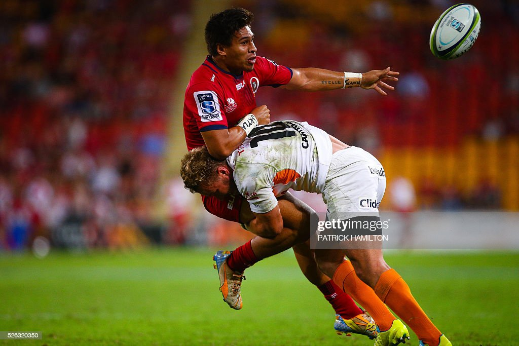 Queensland Reds player Junior Laloifi gets a pass away as he is tackled by Toyota Cheetahs player Fred Zeilinga during the Super Rugby match between Queensland Reds and Toyota Cheetahs at Suncorp Stadium in Brisbane on April 30, 2016. / AFP / Patrick HAMILTON / --IMAGE