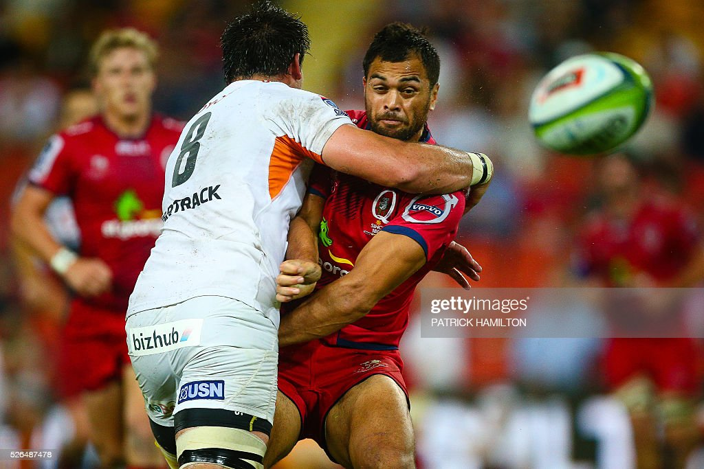 Queensland Reds player Karmichael Hunt (R) gets a pass away as Toyota Cheetahs player Henco Venter (L) completes a tackle during the Super Rugby match between Queensland Reds and Toyota Cheetahs at Suncorp Stadium in Brisbane on April 30, 2016. / AFP / Patrick HAMILTON / --IMAGE