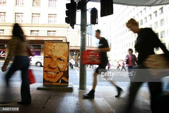 Queenslanders pass by a traffic light signal box in the Brisbane CBD painted with the image of Queensland Premier Peter Beattie who is expected to...