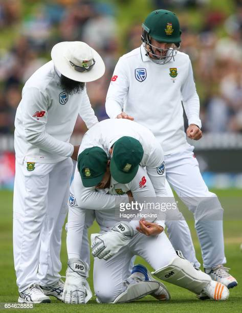 Quentin de Kock of South Africa is congratulated by teammates Faf du Plessis Hashim Amla and Stephen Cook after taking a catch to dismiss Neil Broom...
