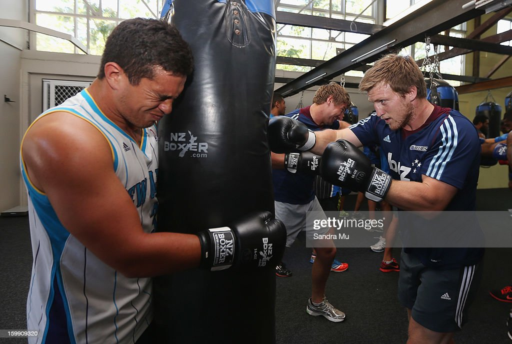 Quentin MacDonald (L) holds the bag for Brendon O'Connor during a Blues training session with Shane Cameron at Shane Cameron Fitness on January 23, 2013 in Auckland, New Zealand.