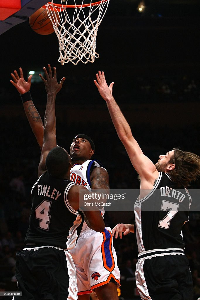 Quentin Richardson #23 of the New York Knicks shoots over Michael Finley #4 and Fabricio Oberto #7 of the San Antonio Spurs at Madison Square Garden February 17, 2009 in New York City.