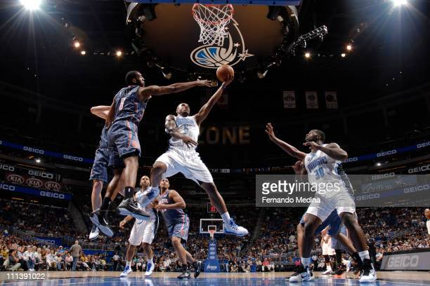 Quentin Richardson of the Orlando Magic shoots against DJ White of the Charlotte Bobcats on April 1 2011 at the Amway Center in Orlando Florida NOTE...