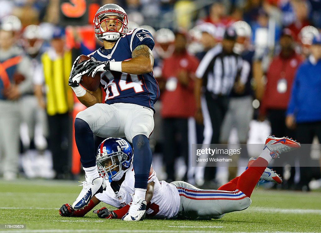 Quentin Sims #84 of the New England Patriots catches a pass in front of <a gi-track='captionPersonalityLinkClicked' href=/galleries/search?phrase=Trumaine+McBride&family=editorial&specificpeople=3972074 ng-click='$event.stopPropagation()'>Trumaine McBride</a> #38 of the New York Giants before running in for a touchdown in the second half during the preseason game at Gillette Stadium on August 29, 2013 in Foxboro, Massachusetts.