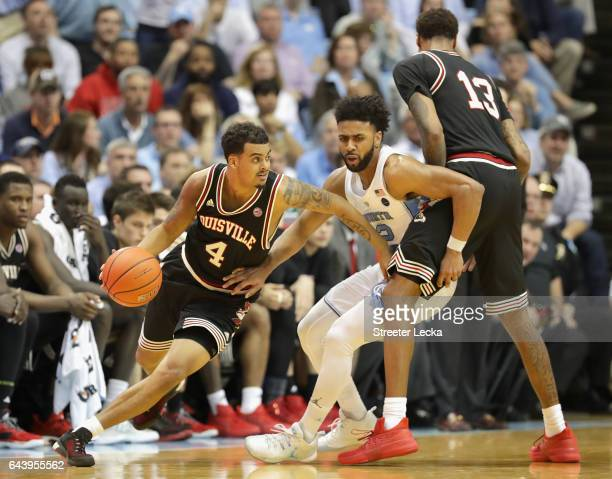 Quentin Snider of the Louisville Cardinals drives around Joel Berry II of the North Carolina Tar Heels during their game at the Dean Smith Center on...