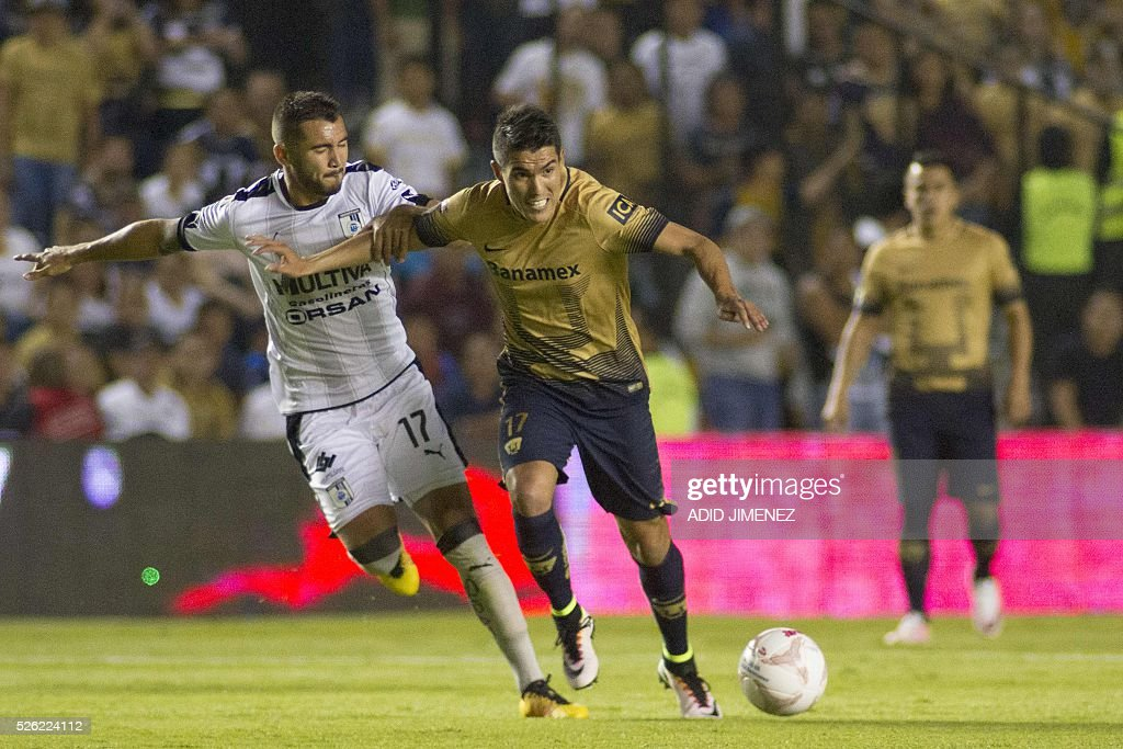 Queretaro's defender Mario Osuna (L) vies for the ball with Pumas's midfielderJose Ruiz (R) during their Mexican Clausura tournament football match at La Corregidora stadium on April 29, 2016, in Queretaro, Mexico. / AFP / ADID