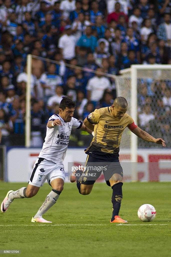Queretaro's midfielder Edgar Benitez (L) vies for the ball with Pumas's defender Dario Veron (R) during their Mexican Clausura tournament football match at the La Corregidora stadium on April 29, 2016, in Queretaro City. / AFP / ADID