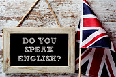 a wooden-framed chalkboard with the question do you speak English? written in it and a flag of the United Kingdom against a rustic wooden background