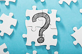 Elevated View Of Question Mark Icon On White Puzzle Over The Blue Background