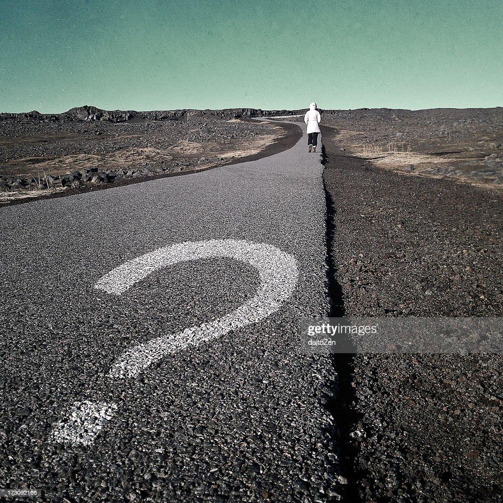 Question mark on asphalt walkway