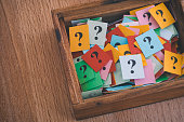 Question marks in a wooden box. Close up.