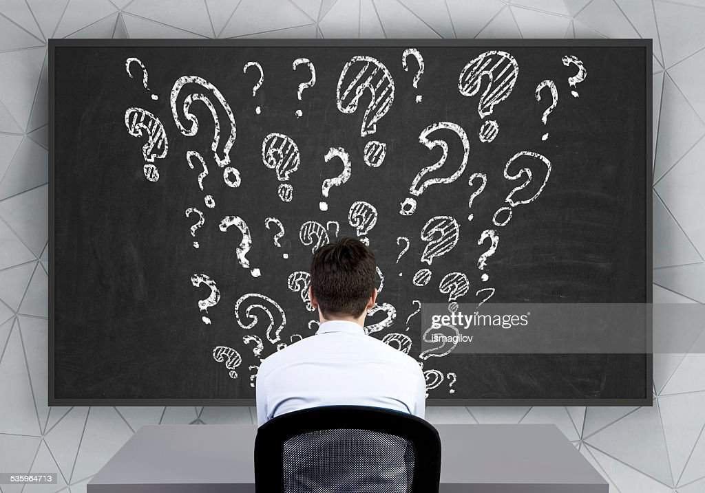 question marks on desk : Stock Photo