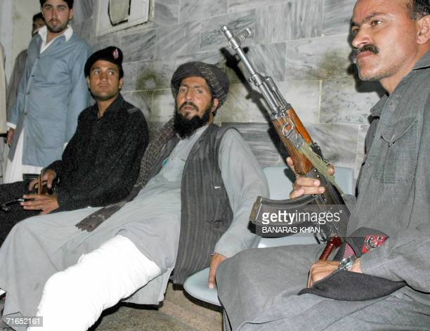 Pakistani policemen escorta group of injured suspected Taliban fighters following their treatment at a hospital in Quetta late 15 August 2006...