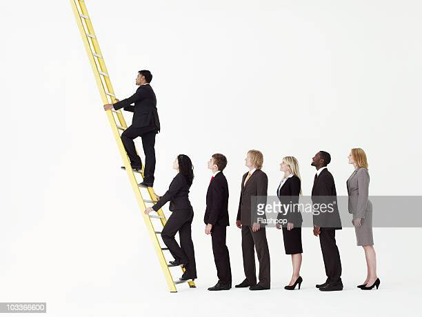 Queue of business people about to climb a ladder