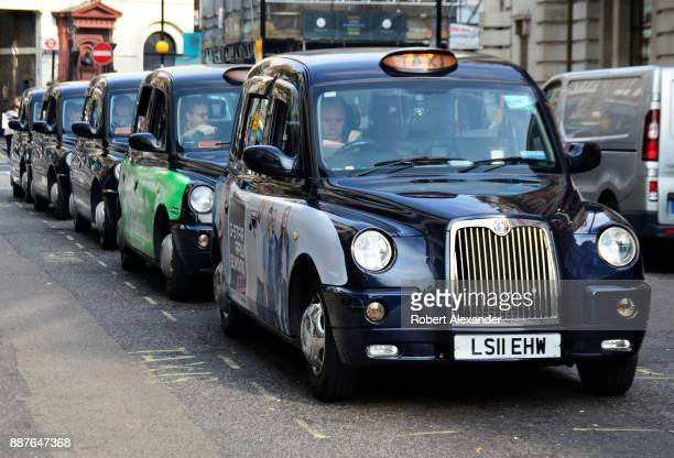 A queue of iconic black taxis and their drivers wait for customers in the Covent Garden district of London England