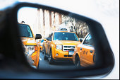 Queue of yellow cabs viewed through wing mirror, New York City, USA