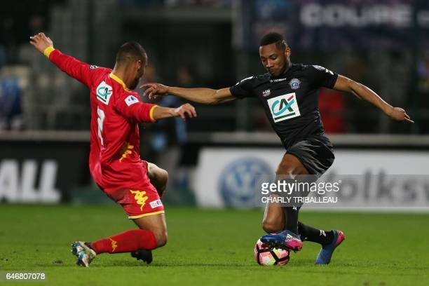 Quevilly Rouen's French defender Cedric JeanEtienne vies with Guingamp's French defender Marcus Coco during the French Cup football match between...