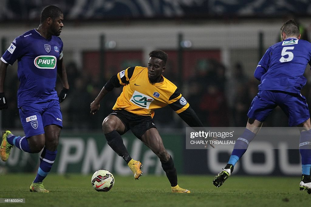 Quevilly's forward Adama Saar (C) vies with Bastia's Malian midfielder Abdoulaye Keita (L) and French defender Mathieu Peybernes (R) during the French Cup football match between Quevilly (USQ) and Bastia (SCB) on January 20, 2015 at the Robert Diochon stadium, in Le Petit-Quevilly, northwestern France. AFP PHOTO / CHARLY TRIBALLEAU