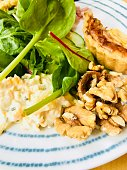 Quiche with mixed salad leaves, walnuts and cheesy coleslaw