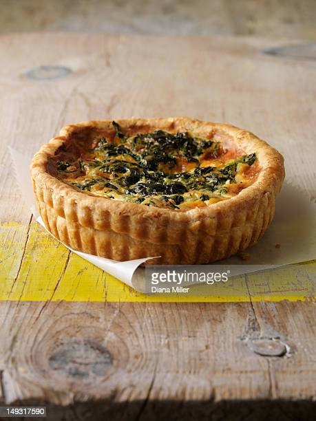 Quiche in paper on wooden table