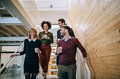 Group of diverse coworkers walking down the stairs in an office, holding paper cups