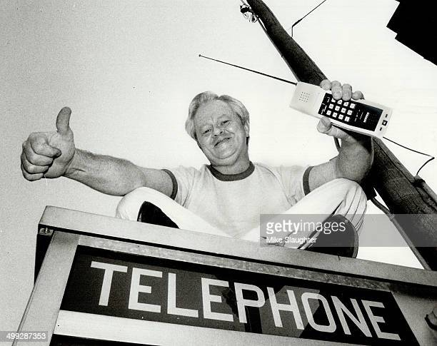 Quick communication Tom Warner and his ultramodern cordless phone sit atop a slightly less modern telephone booth
