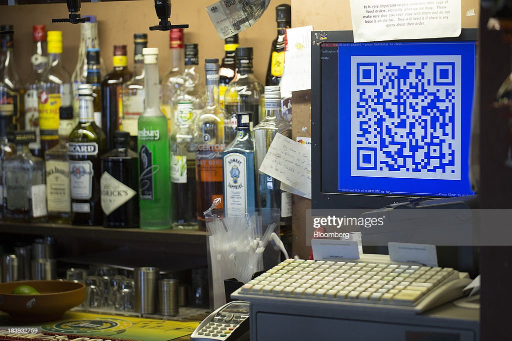 A quick response (QR) code for a Bitcoin purchase is displayed on the monitor of a cash register as bottles of alcoholic spirits sit on the bar at the Pembury Tavern in London, U.K., on Wednesday, Oct. 9, 2013. Bitcoins are being adopted by a few merchants, enabling customers to buy beer at Pembury Tavern in East London, cocktails at EVR bar in New York and dessert at Cups and Cakes Bakery in San Francisco. Photographer: Simon Dawson/Bloomberg via Getty Images