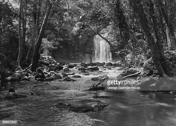 A quiet respite as a member of the expedition enjoys an unidentified waterfall found during a trek 1933 Kenya