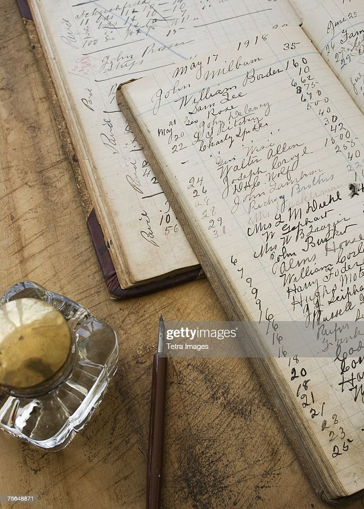Quill pen and ink jar next to old ledger books