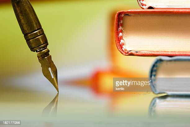 A quill pen and two books in a pile