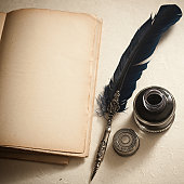 Quill pen,inkwell and old book on a paper with texture. Vignette. Copy space. Soft focus.
