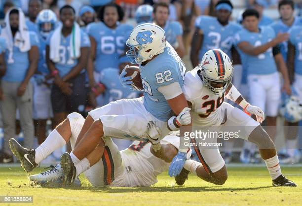 Quin Blanding and Charles Snowden of the Virginia Cavaliers tackle Brandon Fritts of the North Carolina Tar Heels during their game at Kenan Stadium...
