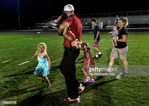 Quince Orchard High School Head Coach John Kelley walks off the field with his family after winning his first game as a head coach on Friday...