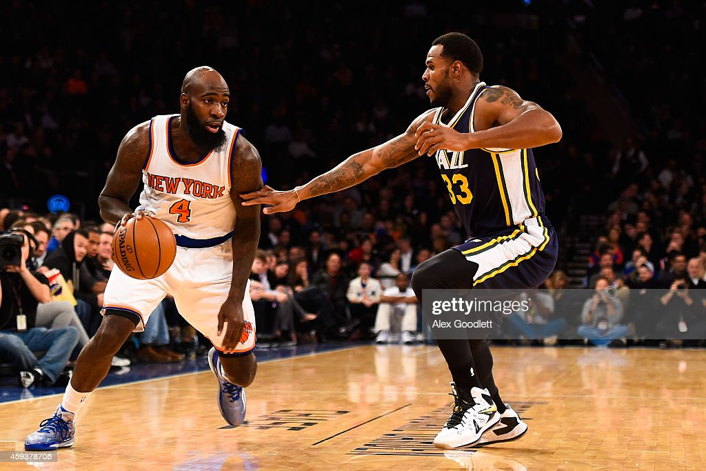 Quincy Acy of the New York Knicks attempts to drive past Trevor Booker of the Utah Jazz at Madison Square Garden on November 14 2014 in New York City...