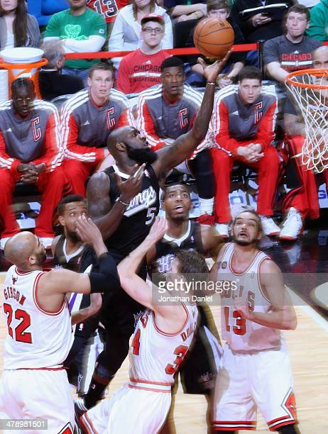 Quincy Acy of the Sacramento Kings puts up a shot over Mike Dunleavy of the Chicago Bulls at the United Center on March 15 2014 in Chicago Illinois...