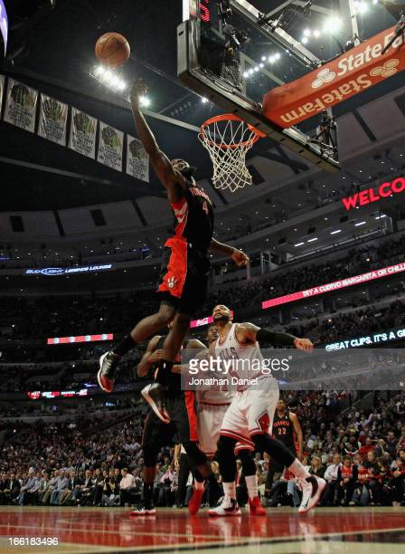 Quincy Acy of the Toronto Raptors leaps for a rebound over Carlos Boozer of the Chicago Bulls at the United Center on April 9 2013 in Chicago...
