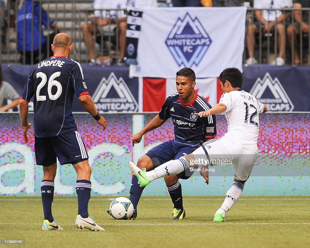 Quincy Amarikwa of Chicago Fire battles for the ball against YoungPyo Lee of the Vancouver Whitecaps during an MLS Match at BC Place on July 14 2013...