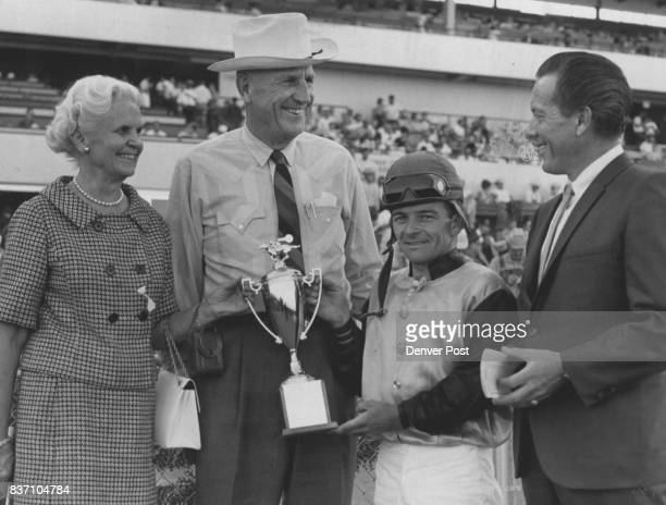 Quincy Farm Owners Collect Trophy Mr and Mrs Ed Honnen hold gold cup presented by Denver Post sports writer George Franco as Lweis joins in...
