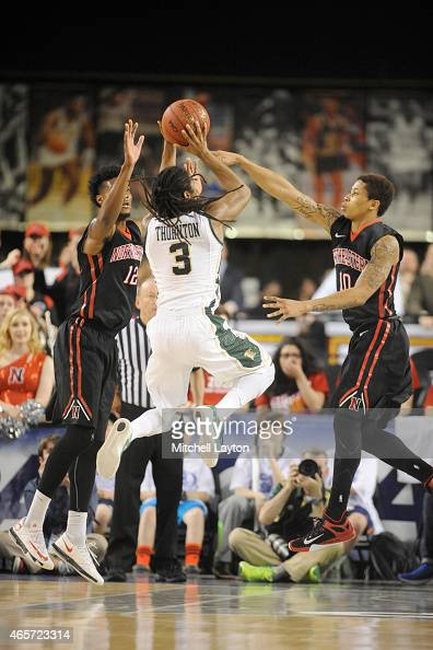 Quincy Ford and TJ Williams of the Northeastern Huskies try to block shot from Marcus Thornton of the William Mary Tribe during the Championships of...