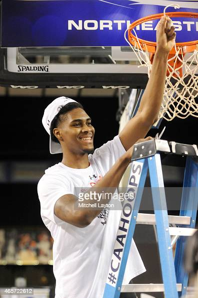 Quincy Ford of the Northeastern Huskies celebrates cutting down the net after winning the the Championships of the CAA Basketball Tournament against...