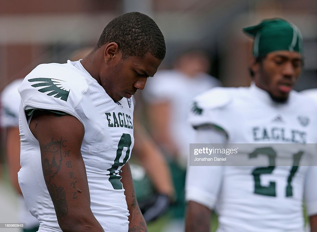Quincy Jones #8 and Ja'Ron Gillespie #21 of the Eastern Michigan Eagles particiapte in a moment of silence for a teammate who was murdered this past week before a game against the Northern Illinois Huskiesat Brigham Field on October 26, 2013 in DeKalb, Illinois.