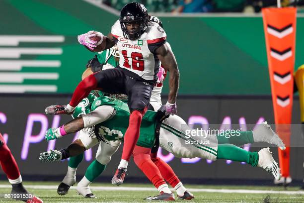 Quincy McDuffie of the Ottawa Redblacks leaps over a diving Trent Richardson of the Saskatchewan Roughriders in the game between the Ottawa Redblacks...